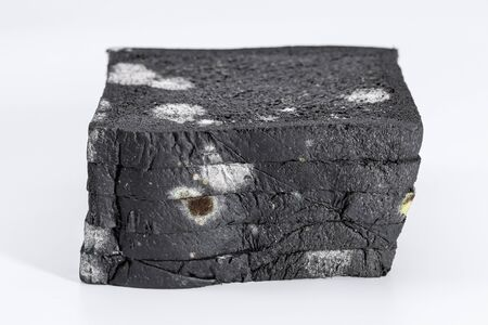Moldy sliced black bread loaf over a white background. Stock Photo