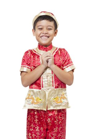 Young Asian boy with Chinese traditional outfit cheongsam or tang suit greeting. Chinese new year concept.