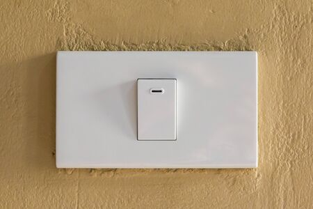 Electrical switch on brown wall.