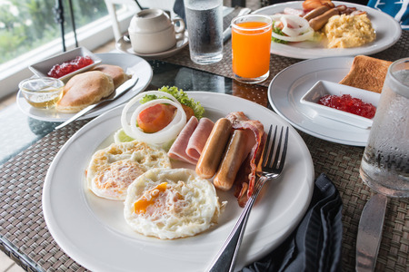 Breakfast with fried egg, ham, sausage, salad, orange juice and Pancakes with strawberry jam and honey on the table.