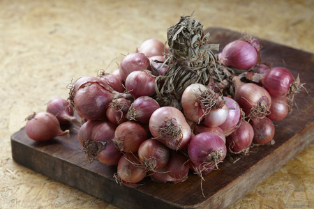 Red shallot onions a group on old chopping wood.