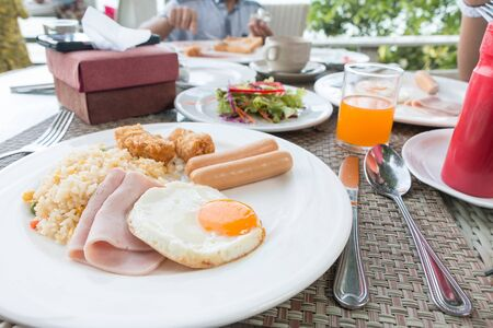 Breakfast with fired rice, fried egg, ham, sausage, fired fish, salad and orange juice on the table.