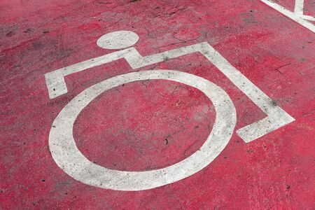 Disabled parking sign on the floor in red on a food center.