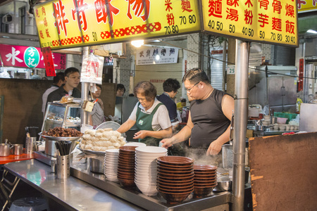 est: Kaohsiung, Taiwan - April 20, 2015: Chief prepares seafood to be sold in Kaohsiung night market. People enjoy food at night market in Taiwan. And is one of the unique culture in Taiwan.