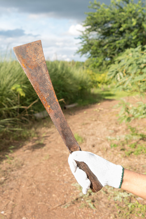 A big rusty knife in a old woman hand on  farm background