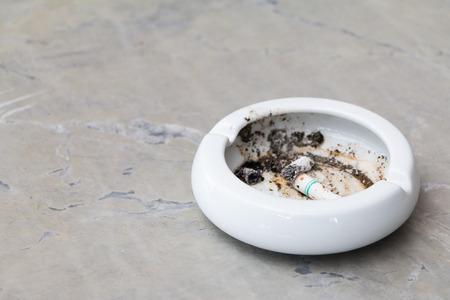 Cigarette with an ashtray on the rock table Archivio Fotografico