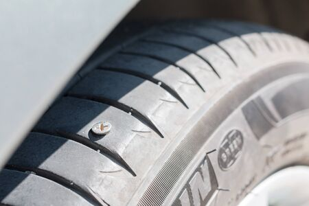 Screw nail puncturing tire. Close up.