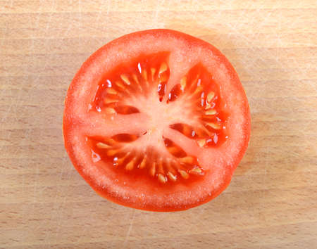 close-up of half tomato on wooden plate