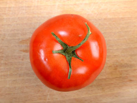 close-up of whole tomato on wooden plate