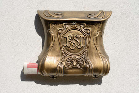 old decorative mailbox on wall with blank newspaper