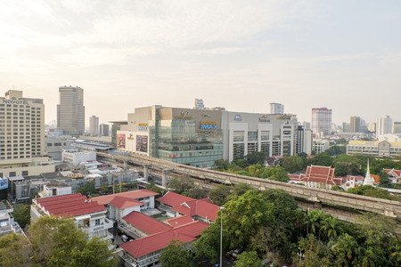 BANGKOK,THAILAND-FEBRUARY 17:Bangkok Mass Transit System (BTS) station at siam paragon and the Pathumwanaram temple at siam in sunny day on February 17,2015