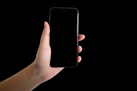 woman hand holding smart phone isolated on black background  photo
