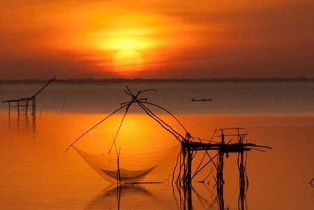 Sun rise and  bamboo machinery  square dip net at canal  Klongyoun canal, Pattalung, Thailand  photo