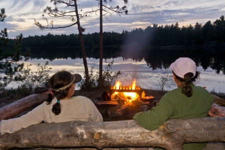 campfires: Two women enjoying a campfire after a day of paddling in the Boundary Waters Canoe Area Wilderness. Stock Photo