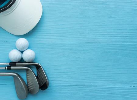 Golfclubs, Golfbälle, Kappe, auf blauem Holztisch, mit Kopienraum.
