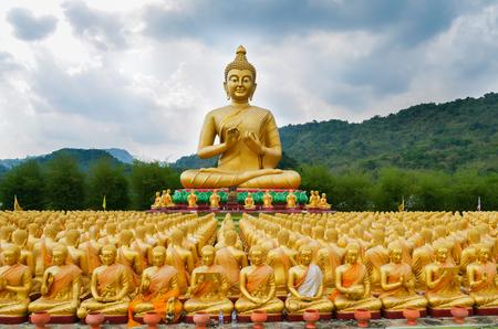 Gran estatua dorada de Buda que rodea por pequeñas estatuas de Buda, en el parque conmemorativo de Buda Makabucha, Nakornnayok, Tailandia Foto de archivo - 78005035