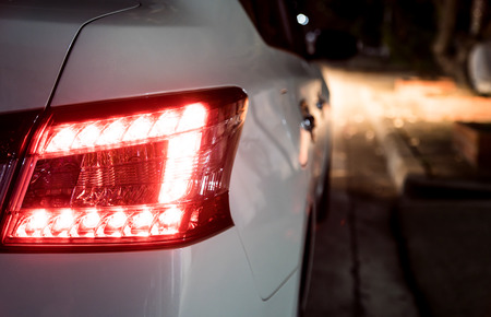 Rear light of white car at night. Break light and head light are active.