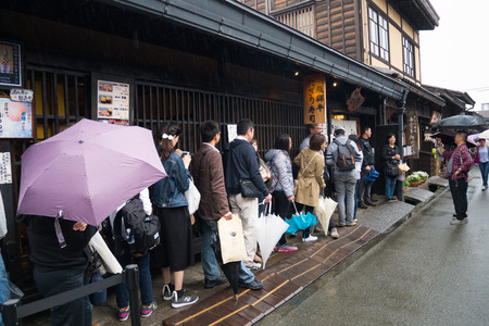 Unknown tourist queing for HIDA Beef sushi, Takayama, Japan. Editorial