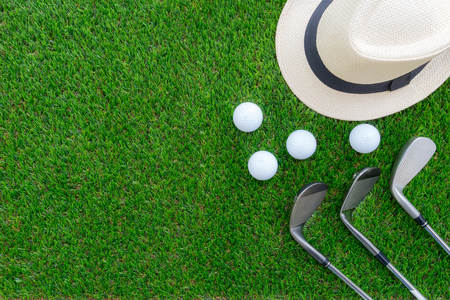 Golf concept : Panama hat, golf balls, golf iron clubs flat lay on green glass, with copy space.