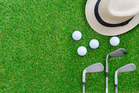 Concepto de golf: sombrero de Panamá, pelotas de golf, palos de hierro de golf en plano sobre vidrio verde, con espacio de copia. Foto de archivo