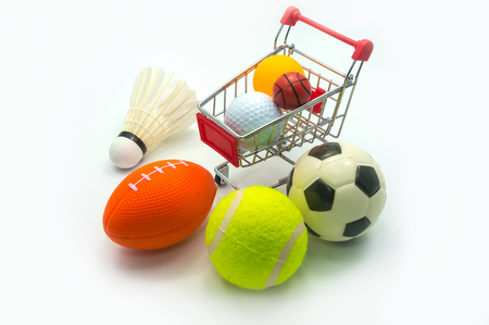 Sports Concept : Various sports balls including, badminton, soccer (football), rugby, tennis, golf, table tennis (ping-pong), small basketball alongside supermarket trolley. On white background.