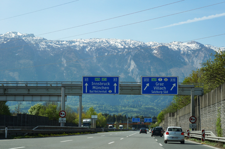 Salzburg, Austria - April 22, 2016 : On Autobahn (German Highway), Road sign indicating direction to Innsbruck and Munich. With beautiful mountain view in background. Editorial