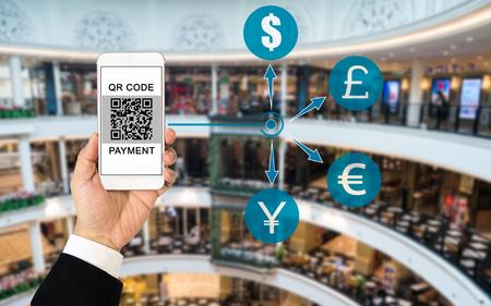 QR-code betalingsconcept: Hand die de vertoningsqr code van de pakholding van de holdingsholding op het scherm met vage achtergrond van winkelcomplex dragen. Verschillende valutapictogrammen die betalingen impliceren, kunnen in elke valuta zijn. Stockfoto