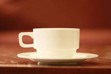white color empty tea cup and saucer on a brown wooden table 版權商用圖片