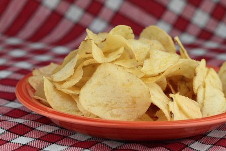 Golden salted potato chips on orange plate. Stock Photo