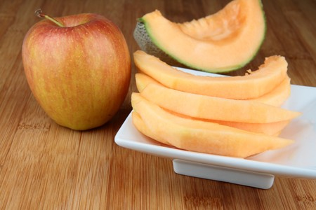 Sliced Cantaloupe melon on white plate and apple on wooden table. photo