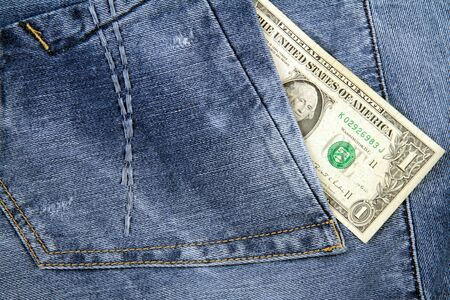 One Dollar in pocket of blue jeans.
