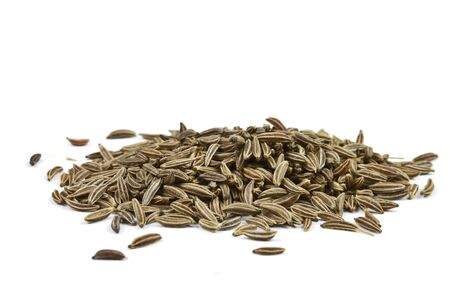 Close-up of cumin seeds on white background.