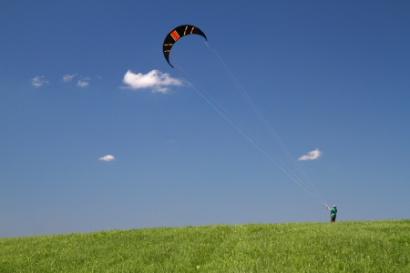 Power free land kiting on green meadow with blue sky