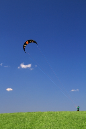 kiting: Power free land kiting on green meadow with blue sky