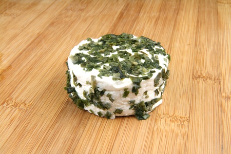 Goat cheese with ramson  wild garlic  and chives on wooden table  photo