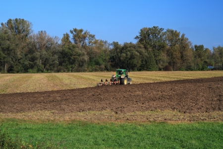 Small tractor plowing in field near the forest  photo