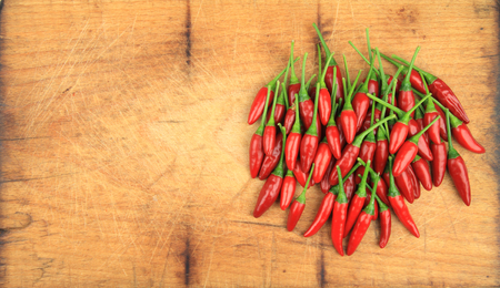 Red chilli peppers on wooden table with place for your text.