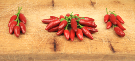 Groups of red chilli peppers on wooden table.