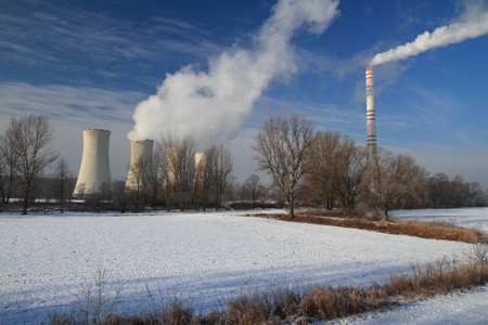 The steam from the cooling towers and smoke from chimney of power plant in winter.