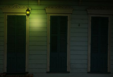 Shotgun house on Royal Street at dusk with yellow light cascading on shutters. photo