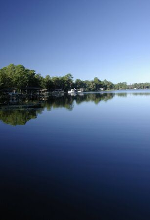Placid early morning light on Florida lake , reflecting a dark blue sky photo