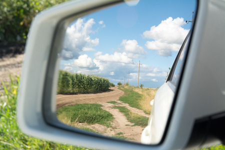Side view mirror reflection of two-lane winding road in field