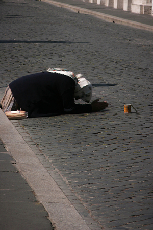 Woman lying on the street asking for money