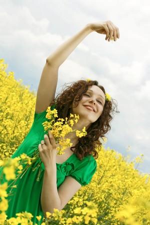 beautiful girl relaxing in a canola field, enjoy the summer photo
