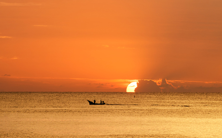 Fishermen out fishing at sunrise in the sea, amidst the clouds and the sky is beautiful
