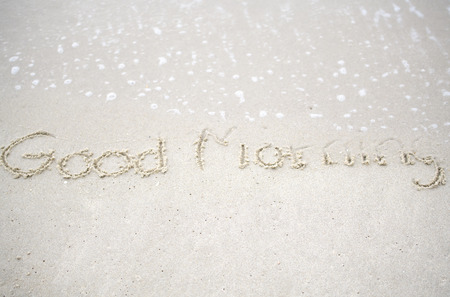 The text Hello morning written on the sand beach by the sea, used in greeting