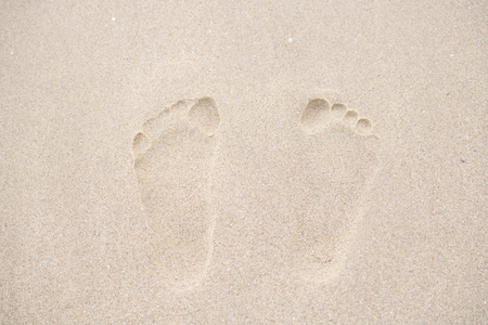 Footprints walking on the beach by the morning, The concept of walking destination