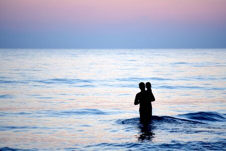 man stood by the sea with his child in his arms and watched the sun rise in the morning. He looked happy and warm