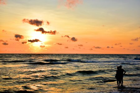 man stood by the sea with his women in his arms and watched the sun rise in the morning. He looked happy and warm Foto de archivo