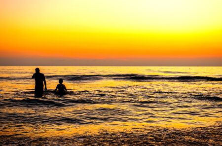 man stood by the sea with his family and watched the sun rise in the morning. He looked happy and warm Foto de archivo